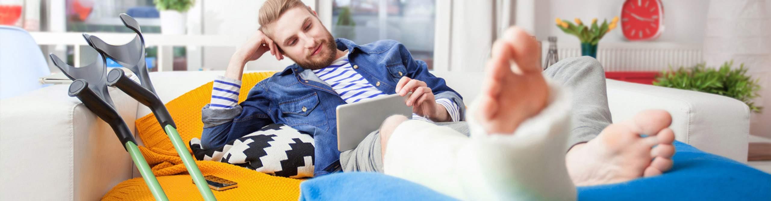 Mann mit Gipsbein schaut lächelnd auf ein Tablet.
