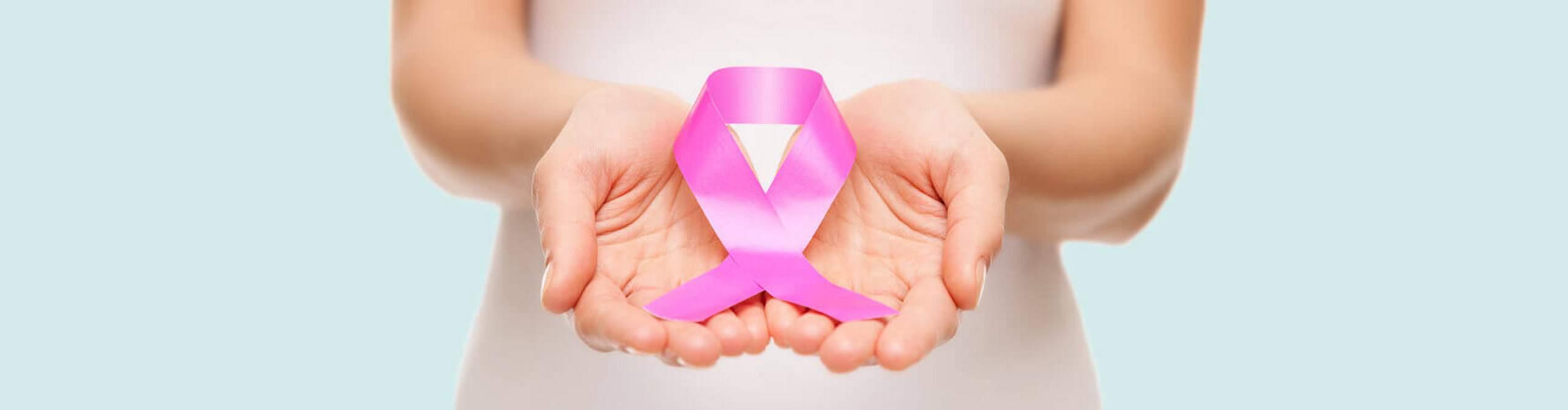 Zwei Hände halten eine pinke Schleife, das Symbol der Brustkrebsfrüherkennung.