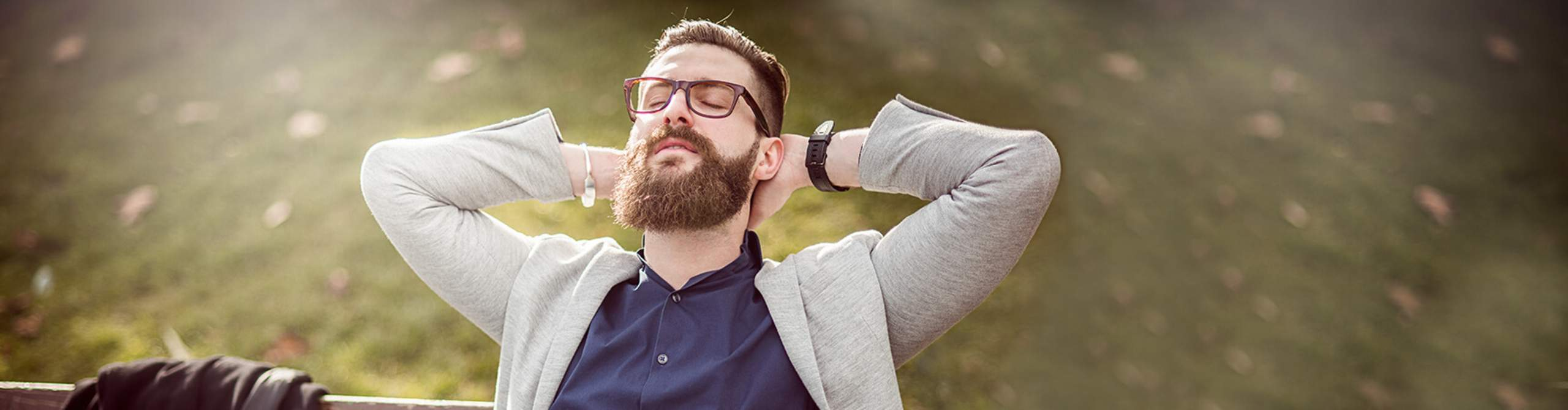 Mann sitzt mit geschlossenen Augen auf einer Parkbank und lehnt sich entspannt zurück.