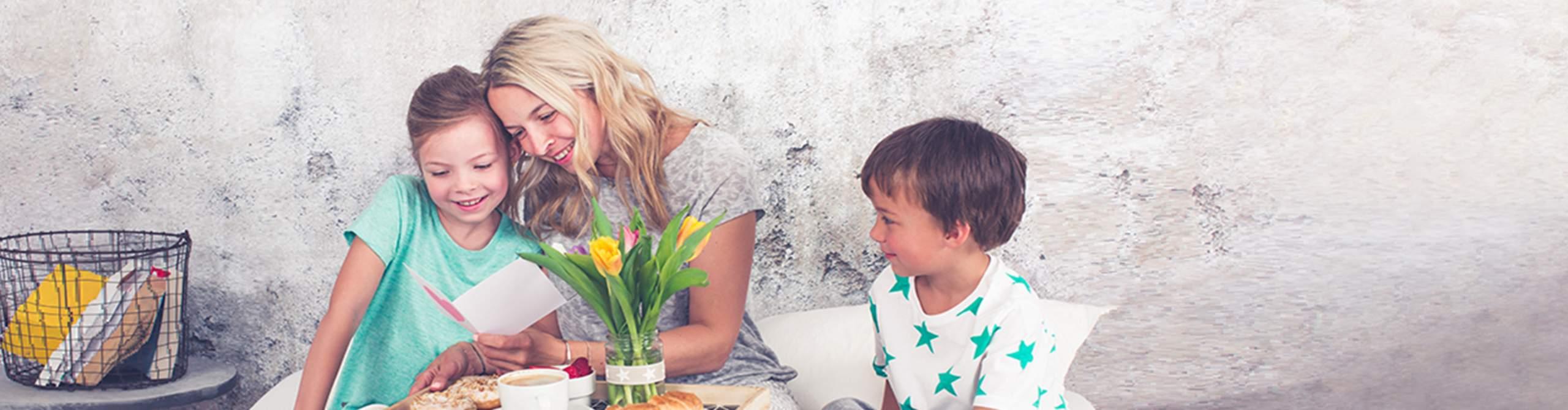Eine Mutter sitzt mit ihren Kindern an einem Tisch und bekommt ein Geschenk.