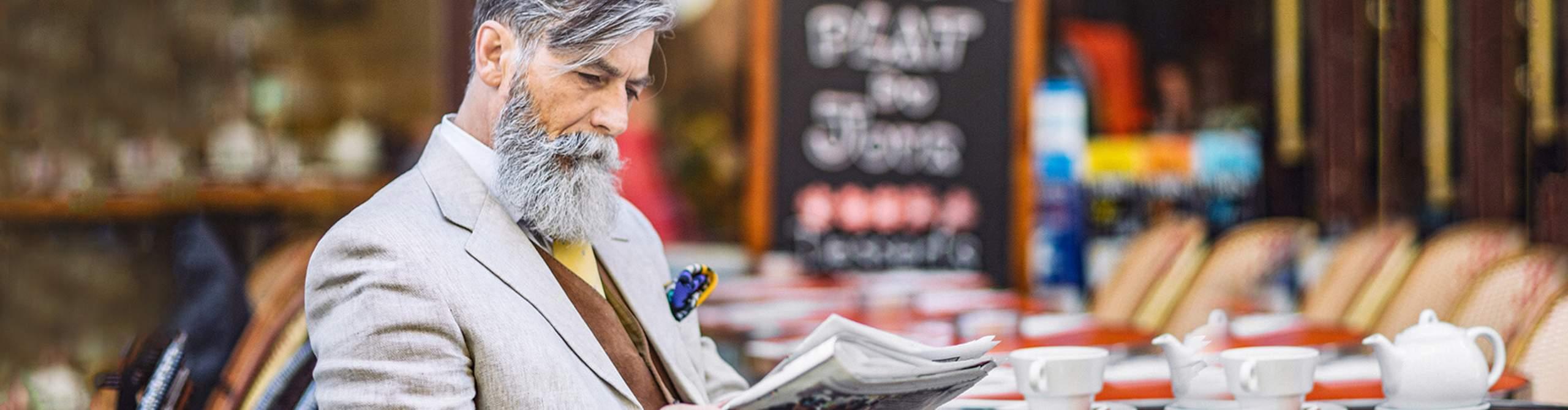 Mann sitzt in einem Cafe und liest Zeitung.