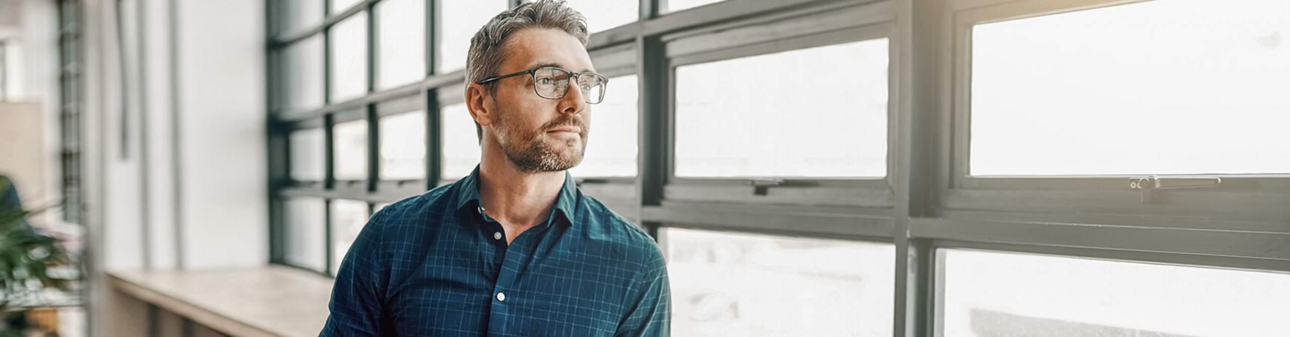 Mann steht in einem modernen Bürogebäude und schaut aus dem Fenster
