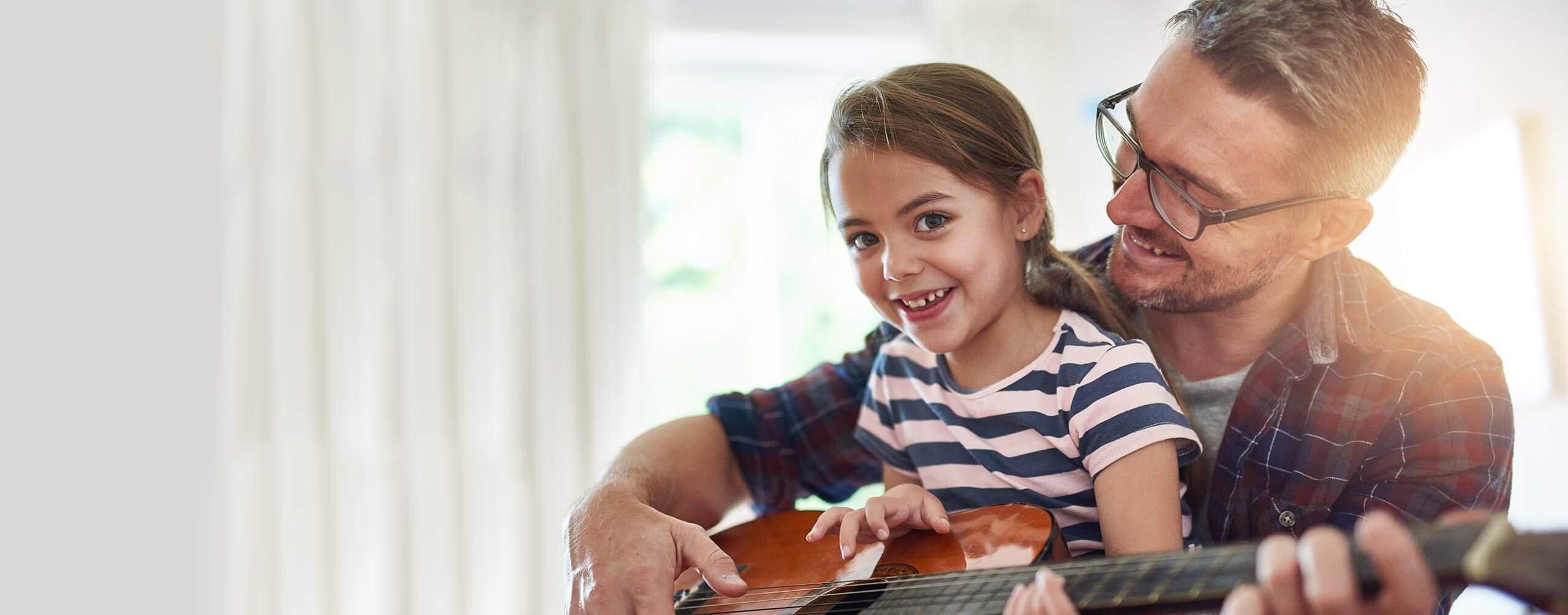 Vater und Tochter spielen zusammen auf der Gitarre.