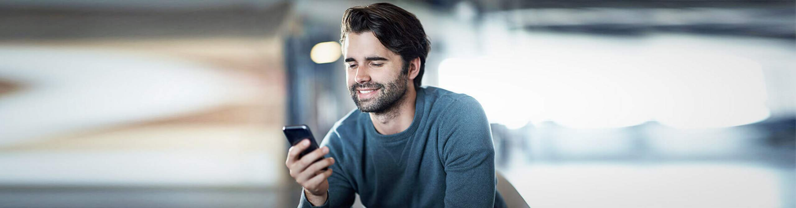 Ein Mann schaut lächelnd auf sein Smartphone.