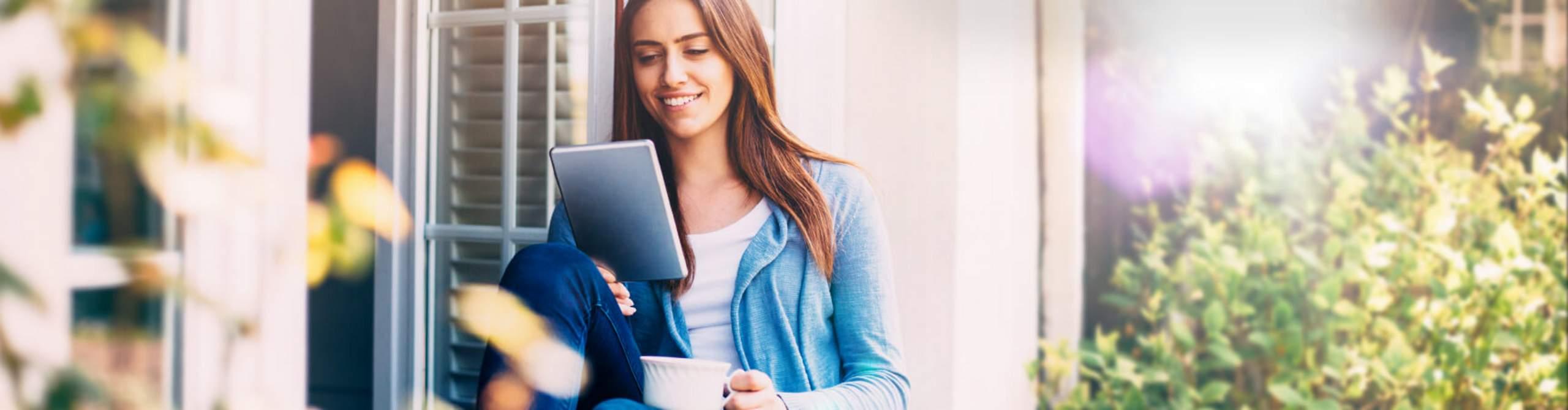 Frau sitzt auf einer Fensterbank und schaut lächelnd auf ein Tablet.