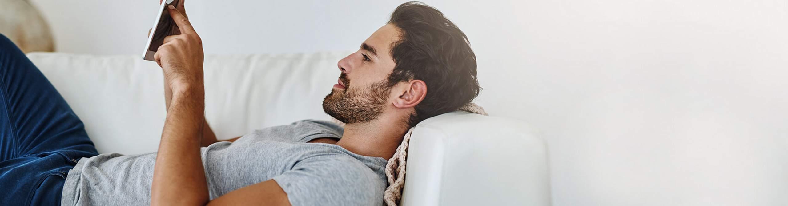 Mann liegt auf dem Sofa und schaut auf sein Smartphone.