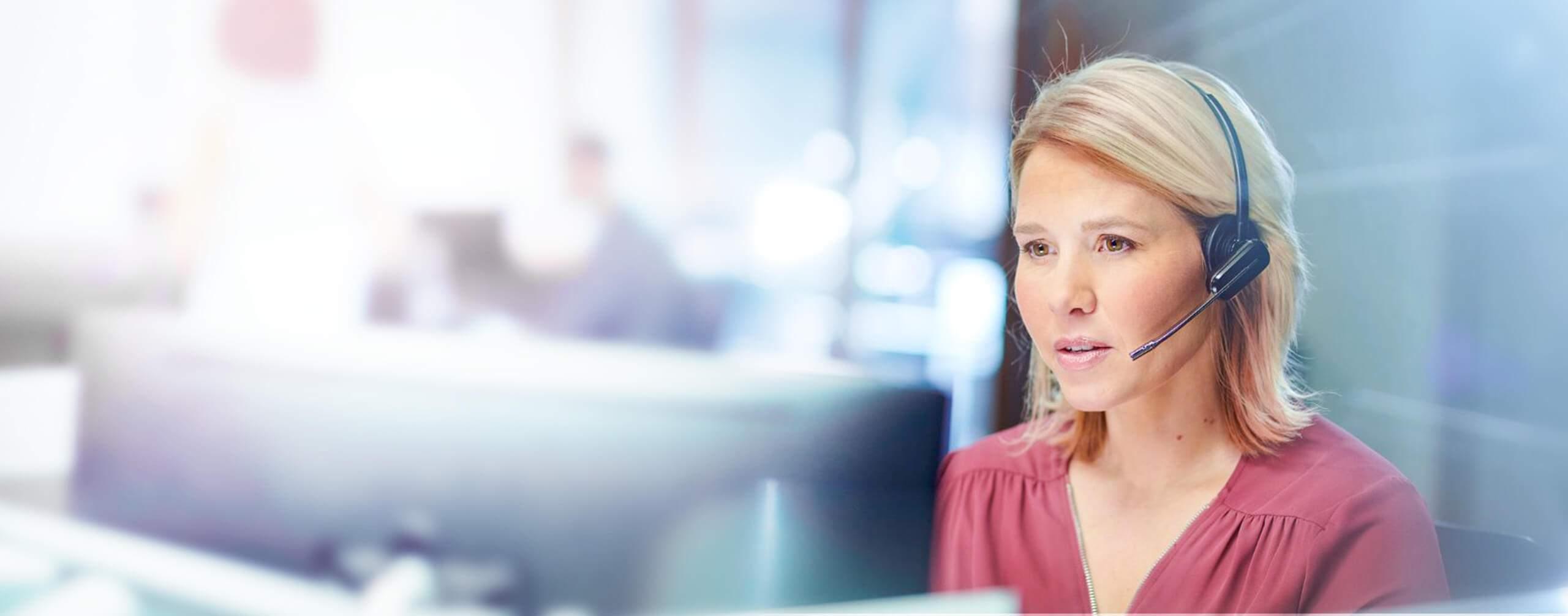 Foto einer Frau in Büroumgebung mit Headset