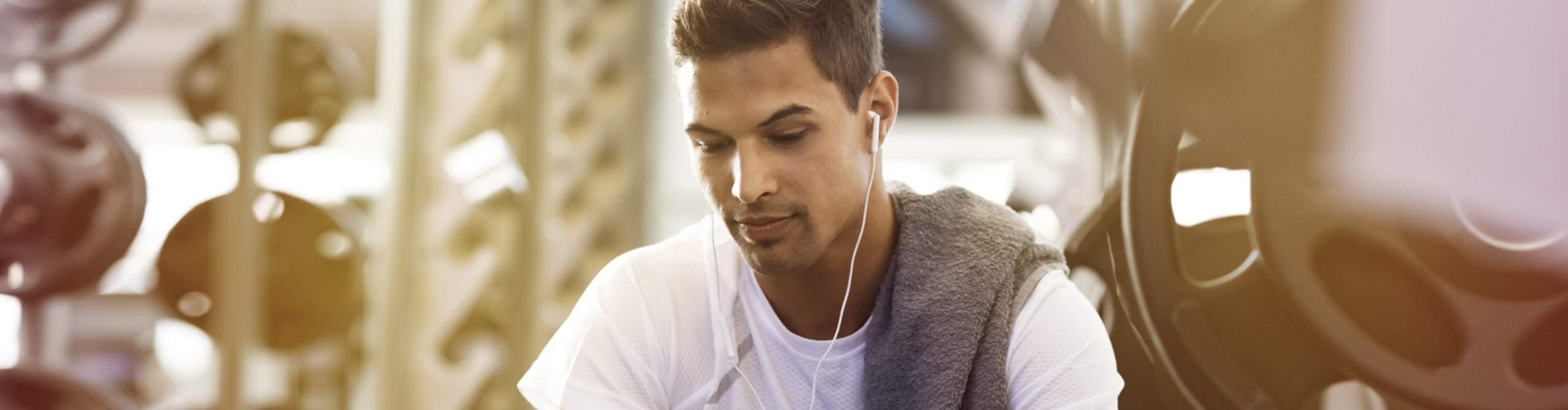 Sportler im Fitnessstudio schaut auf sein Smartphone
