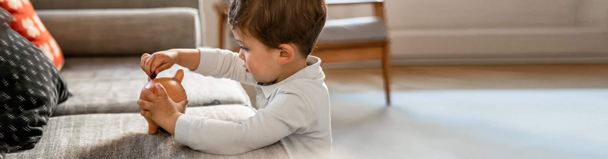 Kind tut eine Münze in eine Spardose.