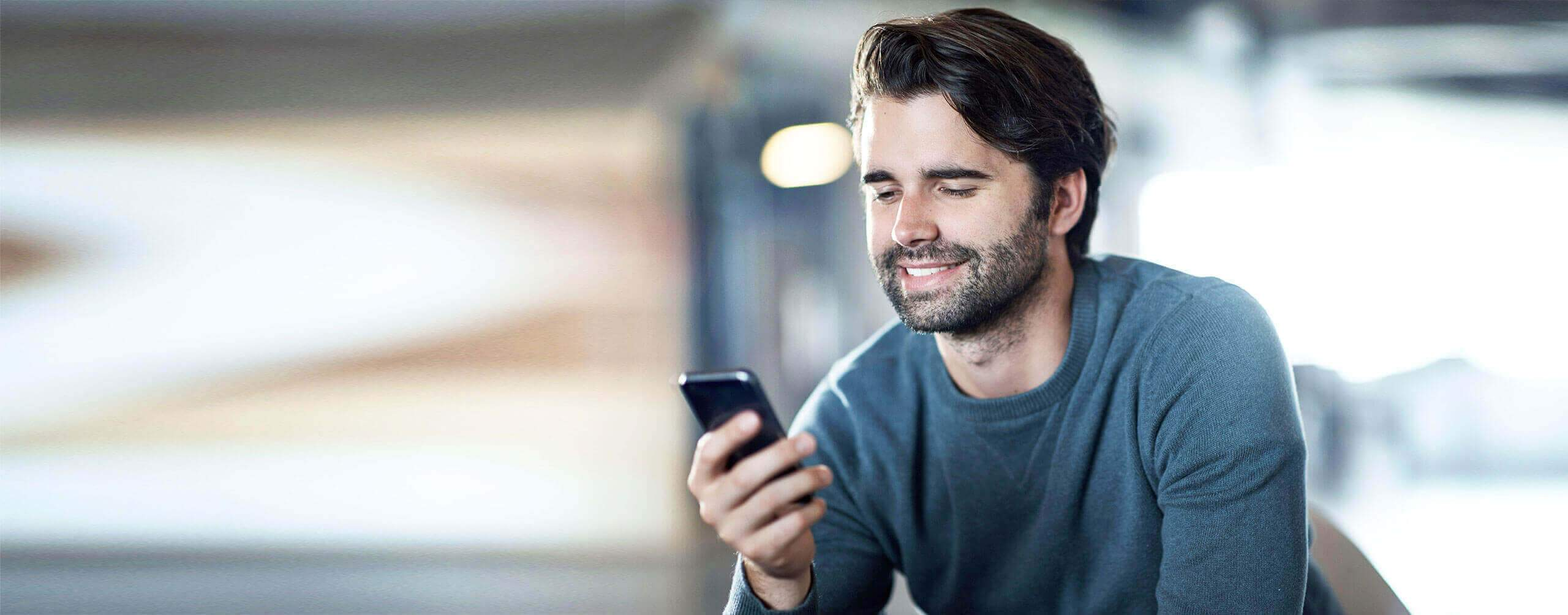 Mann guckt lächelnd auf eine Smartphone