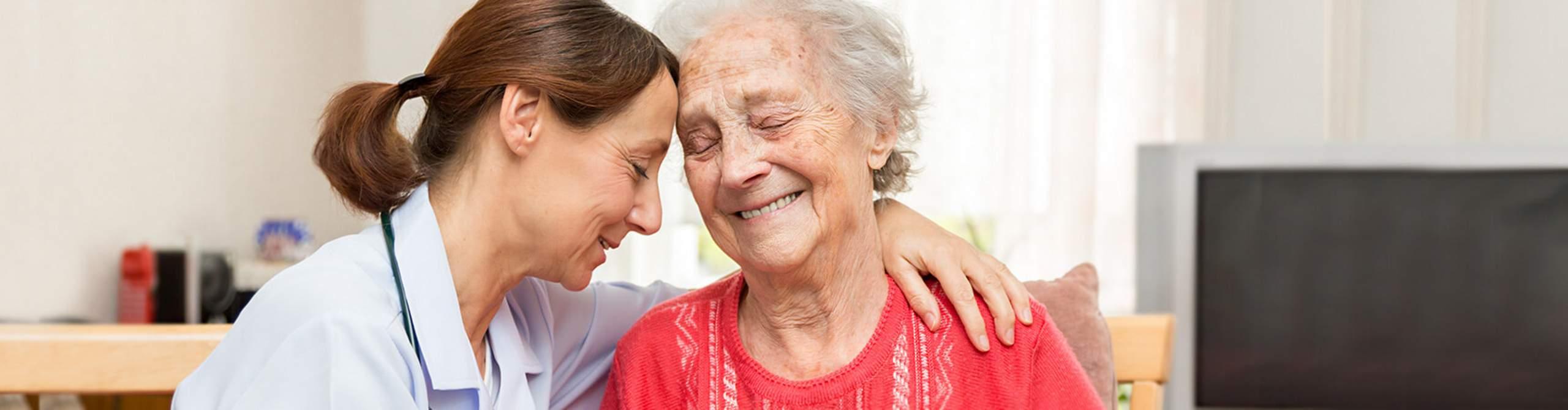 Pflegerin umarmt ältere Frau.