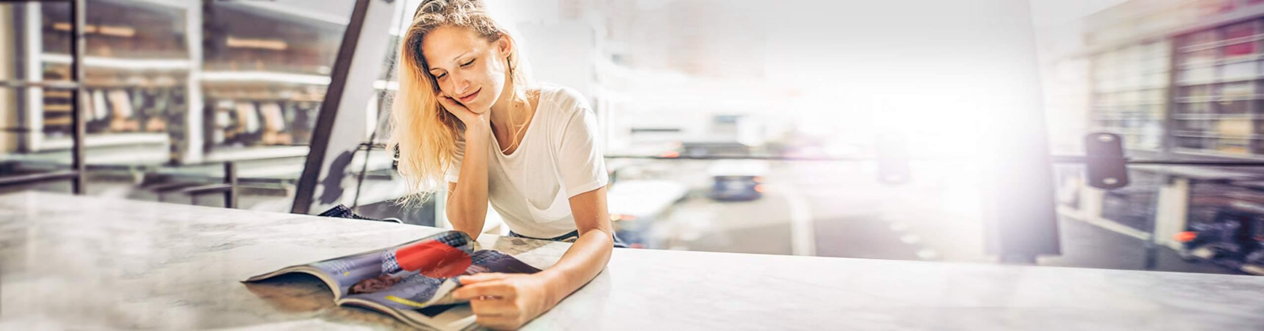 Eine Frau in einem Druckbetrieb liest eine Zeitschrift.