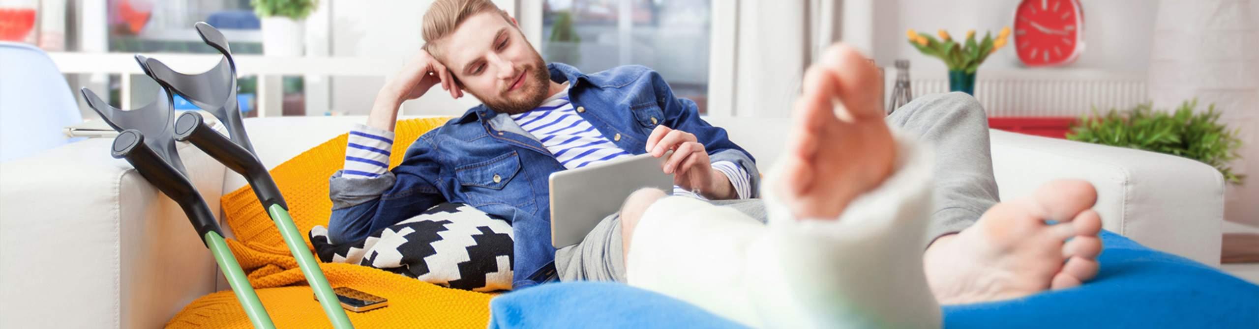 Mann mit Gipsbein recherchiert im Internet