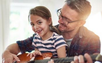 Vater spielt Gitarre mit Tochter auf dem Schoß.