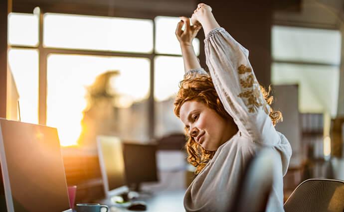 Junge Frau sitzt am Schreibtisch und streckt die Arme