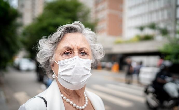 Frau im Seniorinnenalter trägt eine Corona-Schutzmaske
