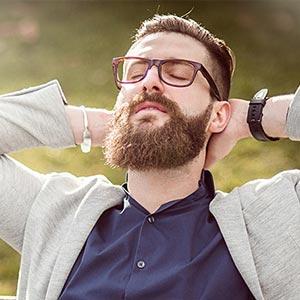 Ein Mann sitzt draußen, schließt die Augen und entspannt.
