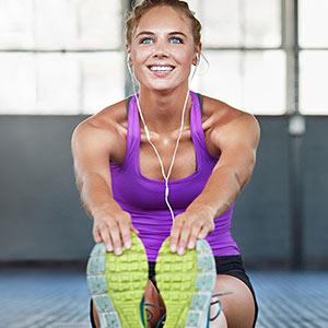 Eine Frau dehnt ihren Rücken vor einer sportlichen Aktivität.
