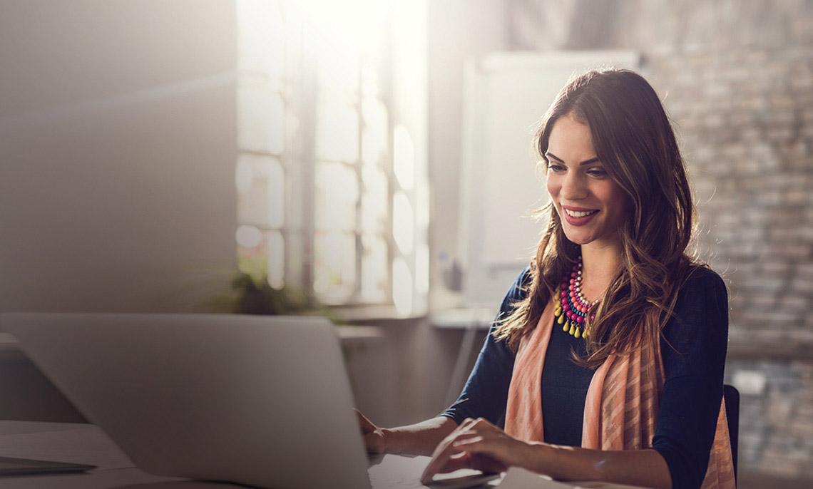 Eine Frau sitzt am Laptop und lächelt.