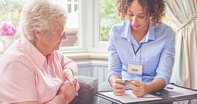 Eine Pflegerin im Gespräch mit einer älteren Dame.