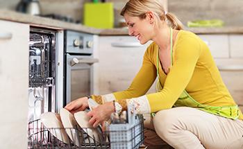 Eine Frau stellt Geschirr in eine Spülmaschine.