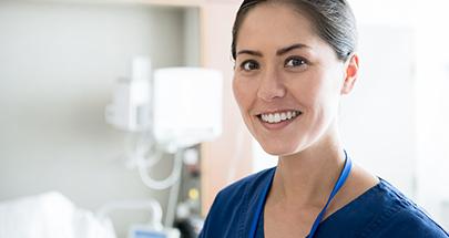 Ärztin in einem Krankenhauszimmer schaut lächelnd den Betrachter an.