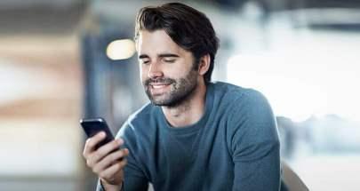 Mann schaut lächelnd auf sein Smartphone.