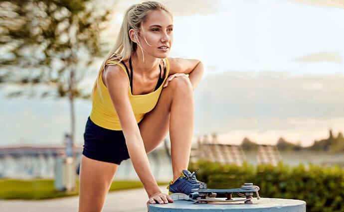 Junge Frau in Sportkleidung macht Dehnübungen im Freien.