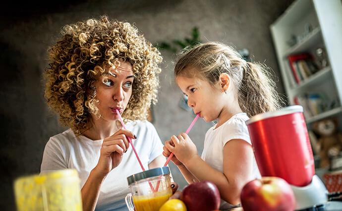 Frau und Tochter trinken selbst gemachte Smoothies